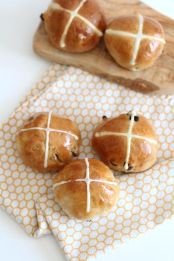Hot cross buns on an orange and white tea towel.