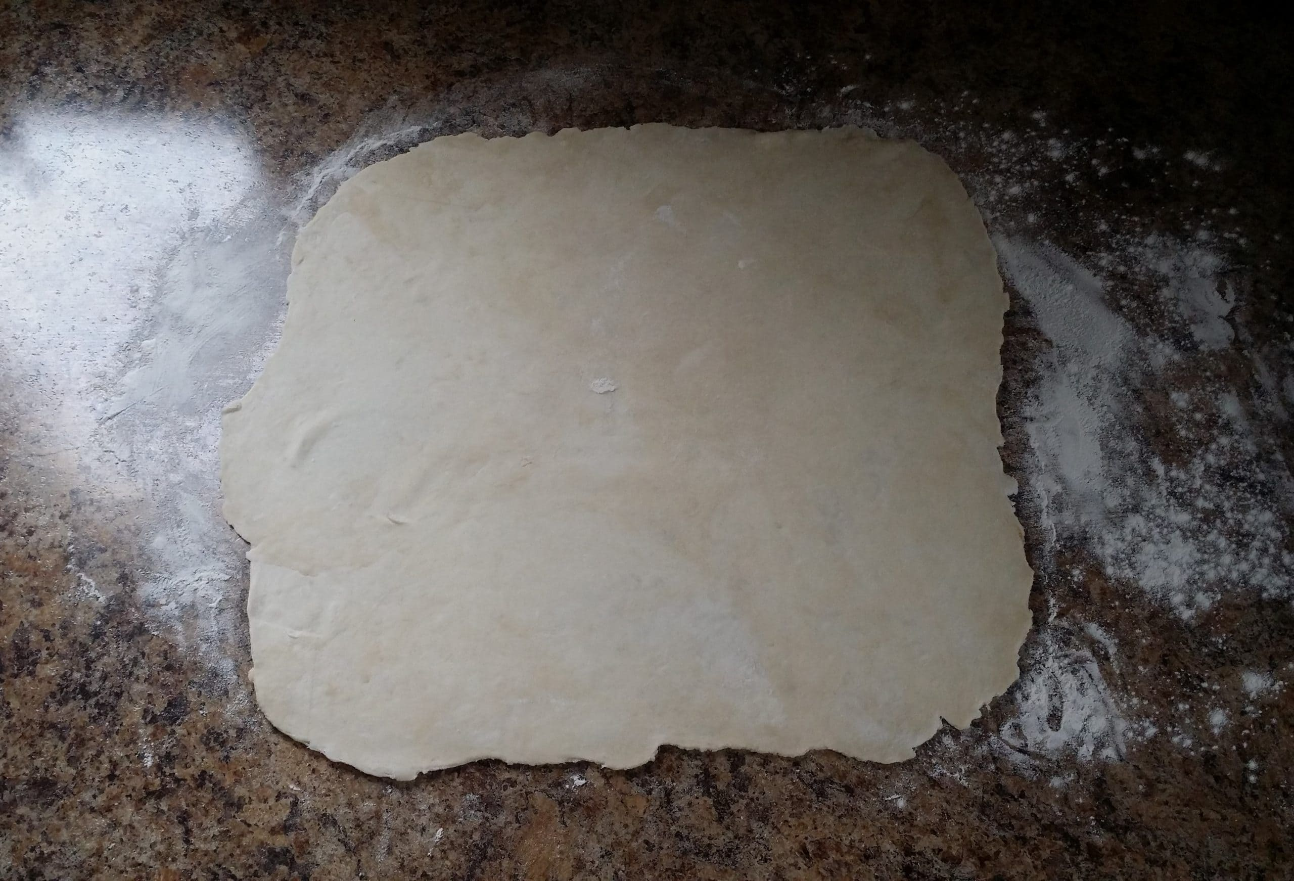 pie dough rolled out on floured surface.
