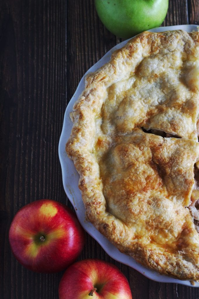 A pie in a pie shell surrounded by apples.